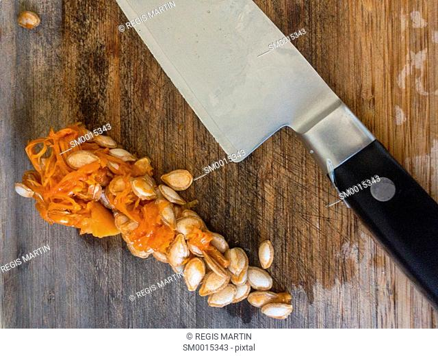 Close-up of a knife and pumpkin seeds on a wooden cutting board