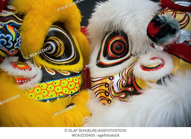 Singapore, Republic of Singapore, Asia - Masks of costume outfits for a traditional lion dance performance are seen in front of a stage in Chinatown