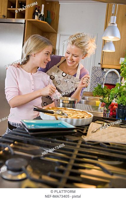 Mother and daughter with a freshly baked pie, Sweden