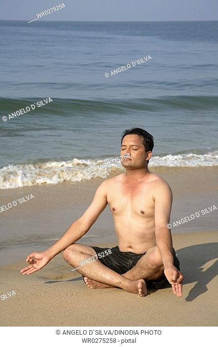 South Asian Indian young man doing yoga sitting in padmasan posture on seashore , Shiroda , Dist Sindhudurga , Maharashtra , India MR703D