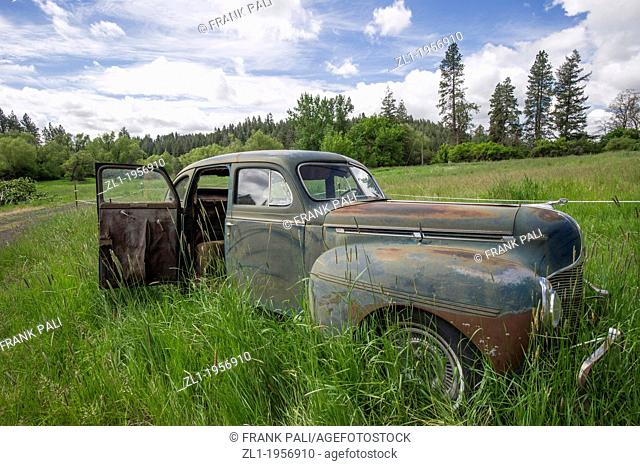 Old car in field with over grown grass.Palouse,Washington USA
