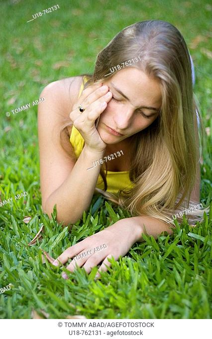 a young blonde girl laying down in the grass with a yellow shirt