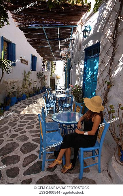 Woman sitting in an open-air cafe at town center, Chora, Amorgos, Cyclades Islands, Greek Islands, Greece, Europe