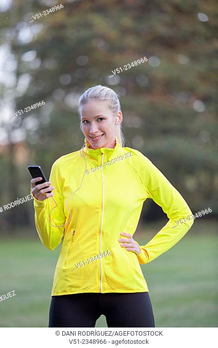 Blonde woman doing sport in park with and headphones smiling at camera