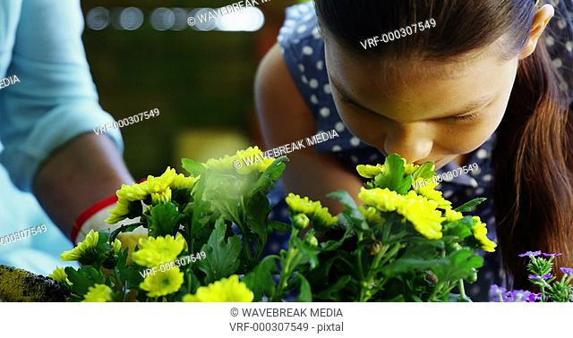 Grandmother and grand daughter smelling flowers