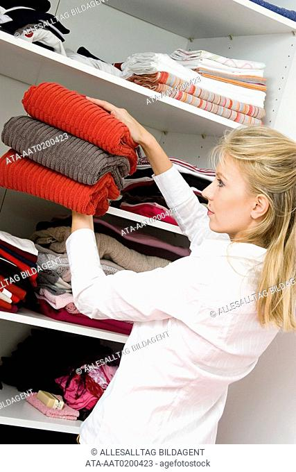 Woman laying towels into the linen cupboard
