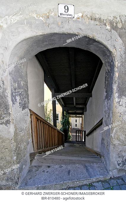Stone archway at the top of covered wooden steps in the historic centre of Hall, Tirol, Austria