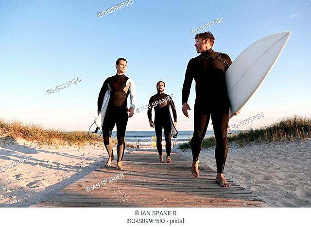 Three surfers walking on boardwalk