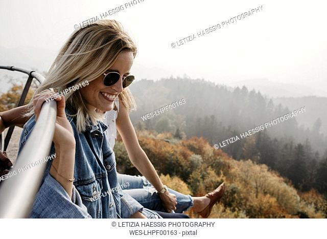 Germany, Black Forest, Sitzenkirch, two happy young women sitting at Sausenburg Castle above mountain forest