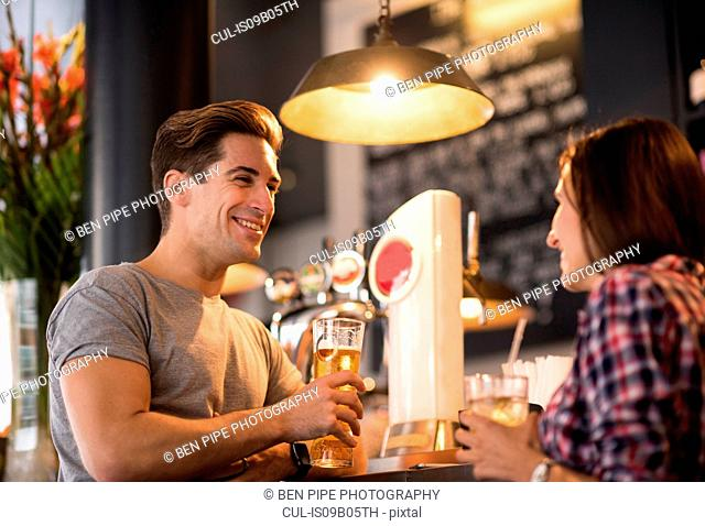 Young couple talking at bar in evening