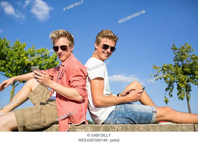 Germany, Two young men sitting on wall using their smart phones