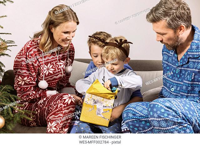 Parents watching son unwrapping a Christmas gift