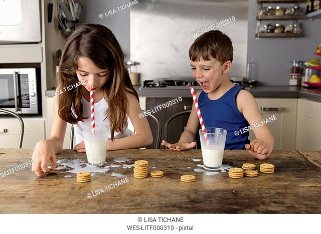 Little girl sitting blowing bubbles in a glass of milk while her brother watching