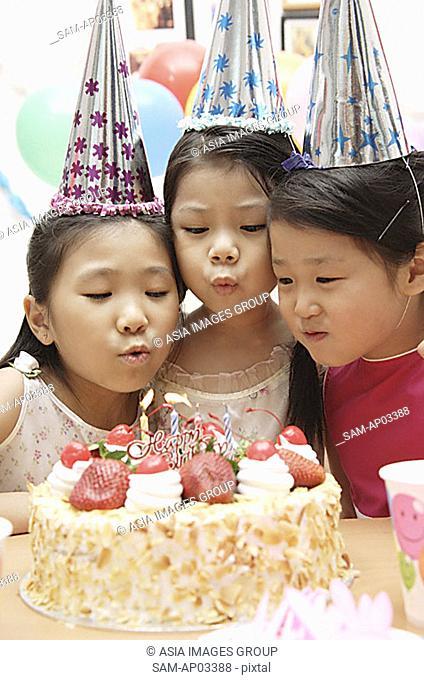 Three girls celebrating a birthday, blowing birthday candles