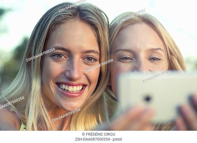 Friends posing for smartphone selfie