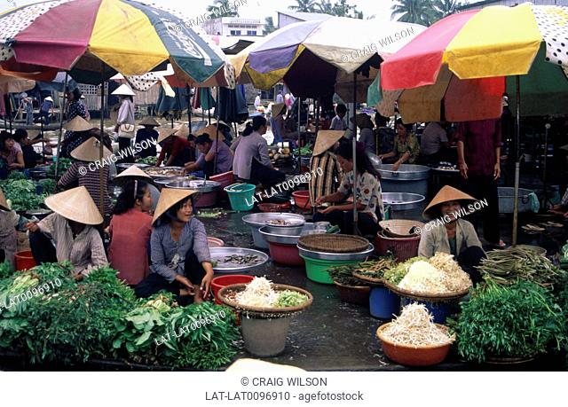 The busy market place with women at food stalls,with piles of fresh fruit and vegetables,food on display