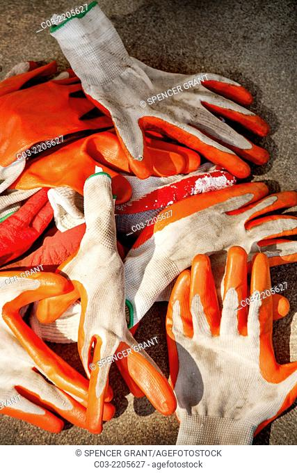 A random pile of orange rubber work gloves forms an abstract pattern at a painting job site