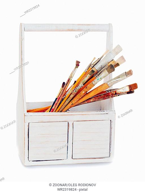 old wooden box with paint brushes isolated on whit