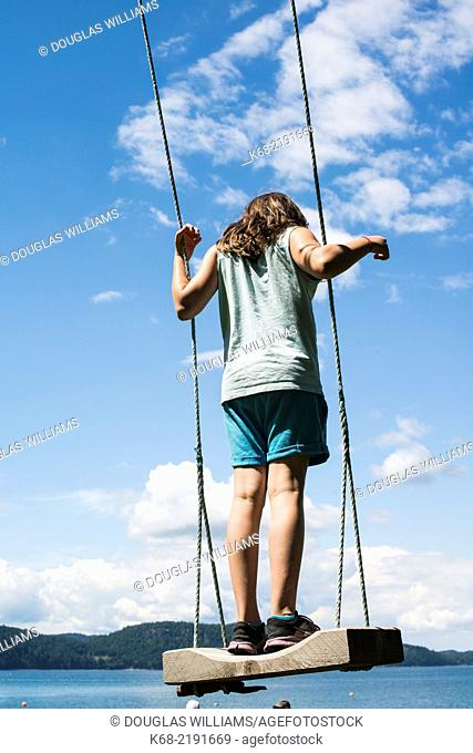 An eleven year old girl stands on a swing on Saturna Island , BC , British Columbia , Canada , Canada