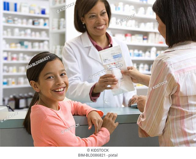 Mother and daughter filling prescription in drug store