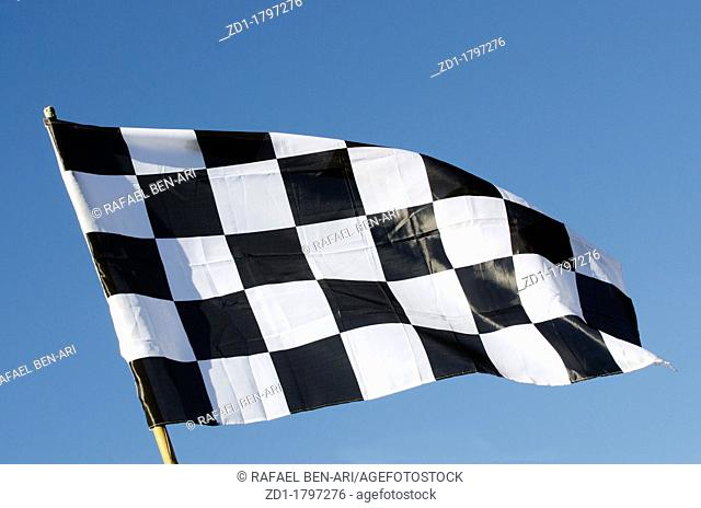 Checkered flag and blue sky during racing in a speedway