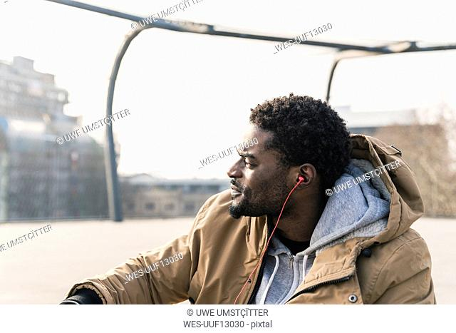 Portrait of young man with earphones outdoors