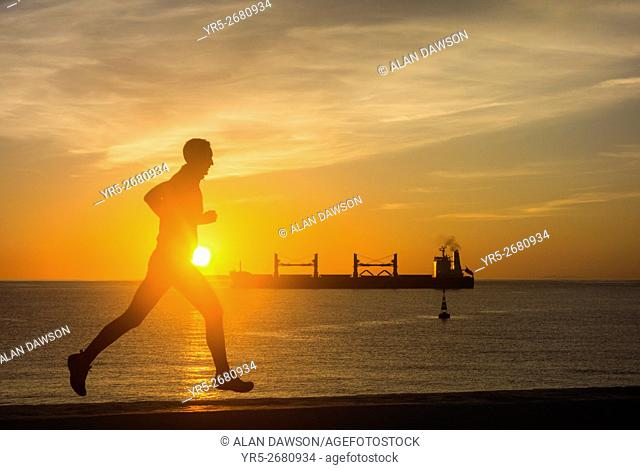A jogger stops to watch the sun rise over the Atlantic Ocean from Avenida Maritima in Las Palmas, Gran Canaria, Canary Islands, Spain,