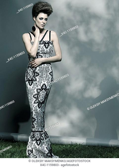 High fashion photo of a beautiful woman wearing elegant long dress