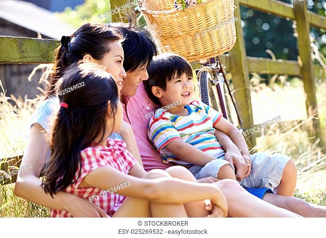Asian Family Resting By Fence With Old Fashioned Cycle