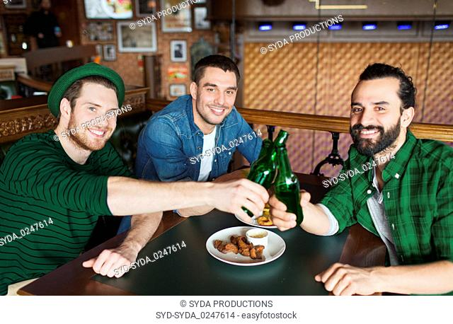 friends drinking beer in bottles at bar or pub