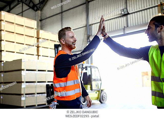 Happy colleagues in protective workwear high fiving in factory