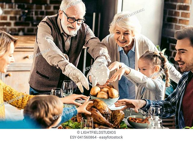 happy family reaching for turkey on thanksgiving table