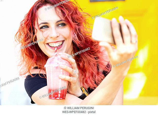 Portrait of laughing woman taking selfie with smartphone while drinking smoothie