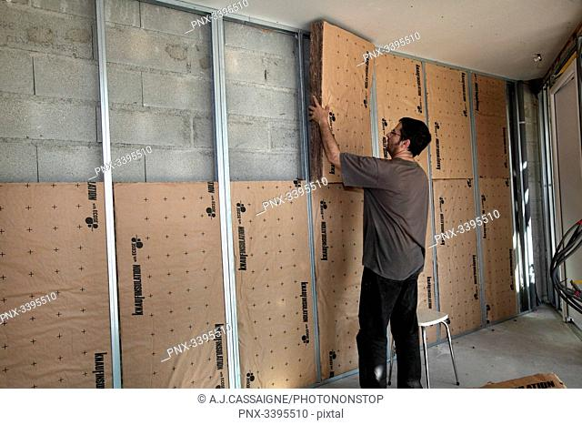 France,House building, wall insulation with glass wool panels on metal rails