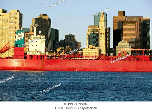 Bright red cargo ship travels in front of Boston Harbor and the Boston skyline at sunrise as seen from South Boston, Massachusetts, New England