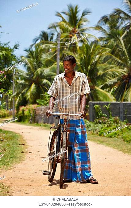 Man with old bicycle in a village in Sri Lanka