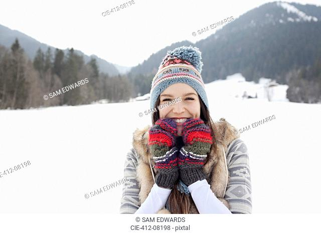 Portrait of enthusiastic woman wearing knit hat and gloves in snowy field