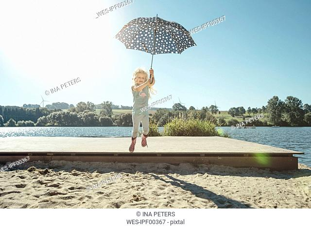 Girl with umbrella jumping off a jetty on a sunny day