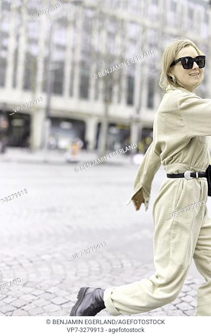 stylish woman wearing latest fashion trends at street during fashion week, in Paris, France