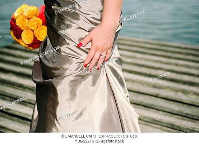 Bride's hand with red nail polish and bouquet