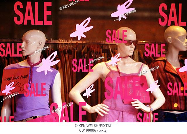 'Sale' signs in front of dummies in shop window