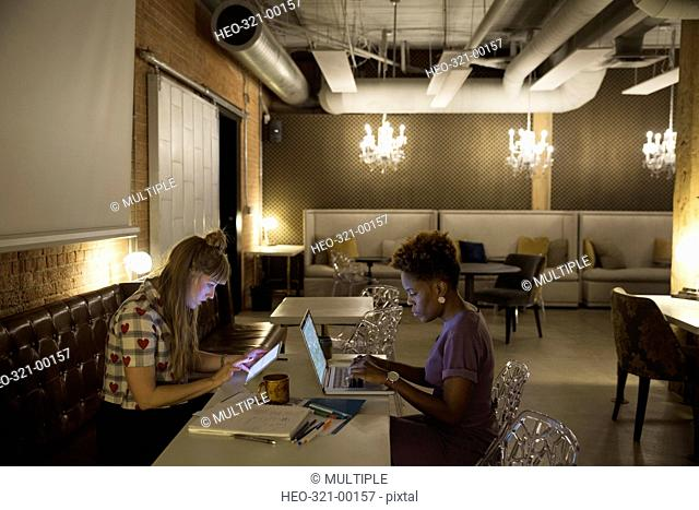 Female designers working late at laptop and digital tablet in office