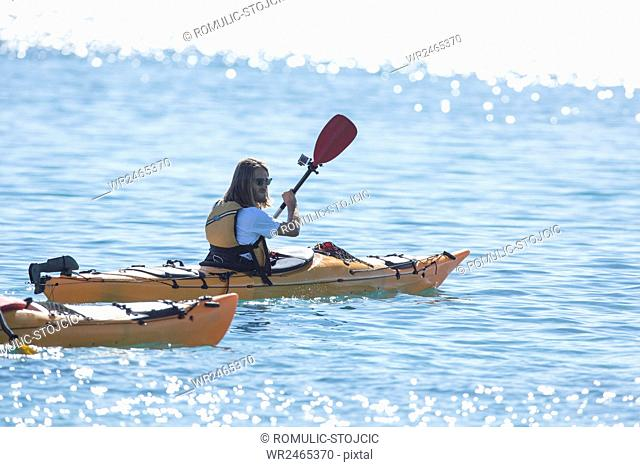 Mid adult man kayaking on river in bright sunshine