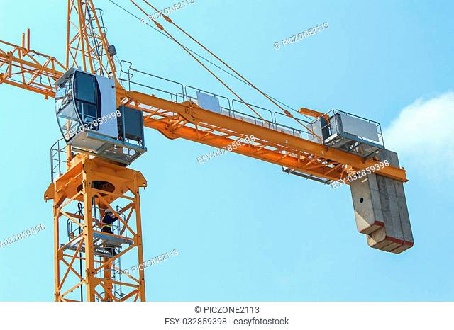 yellow tower crane with clear blue sky
