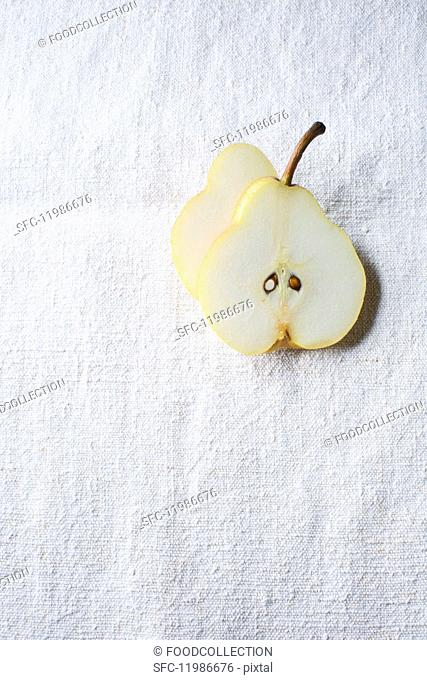 A sliced pear on a white surface