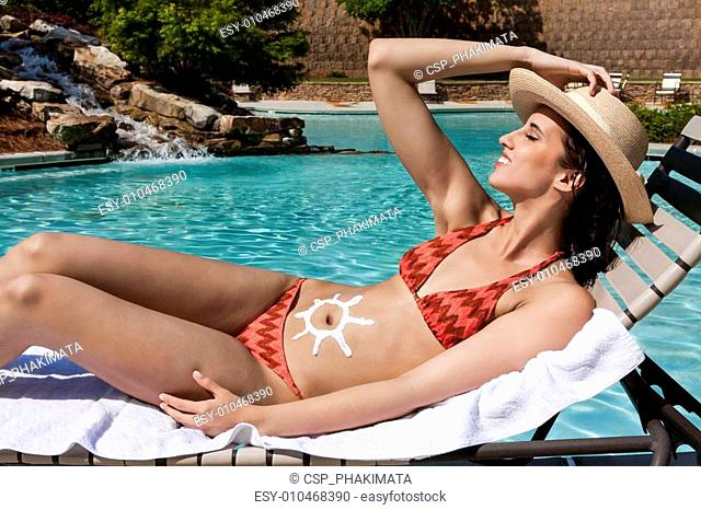 Sun tanning woman at pool