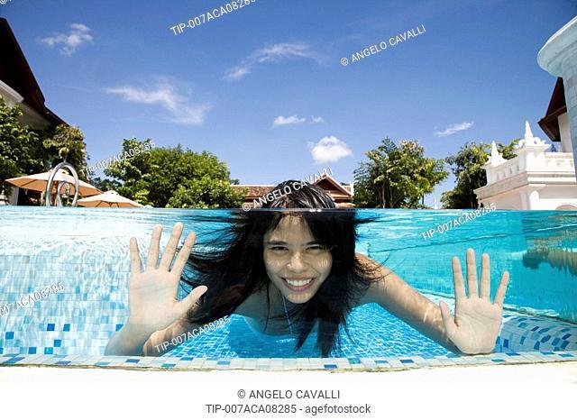 Woman in swimming pool at Dhevi Mandarin Oriental resort, Chiang Mai, Thailand