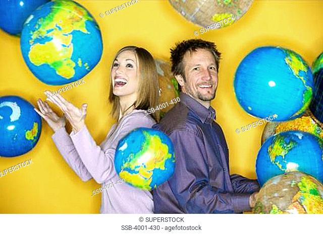 Businessman and a businesswoman posing with globes