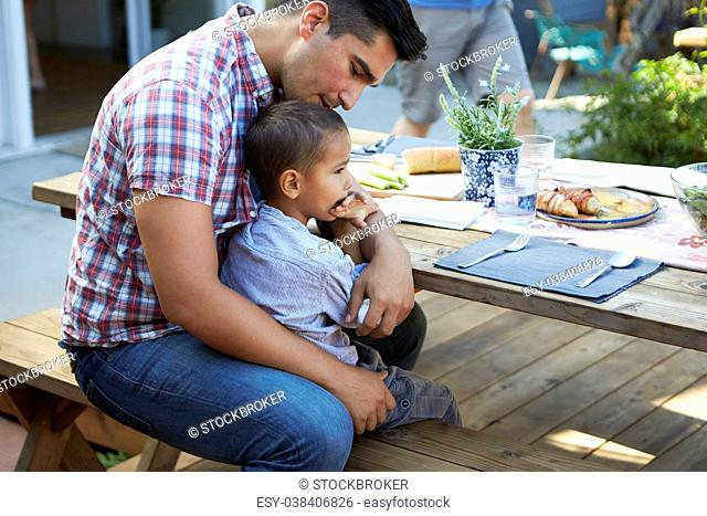 Father And Son Sitting At Table For Outdoor Meal In Garden