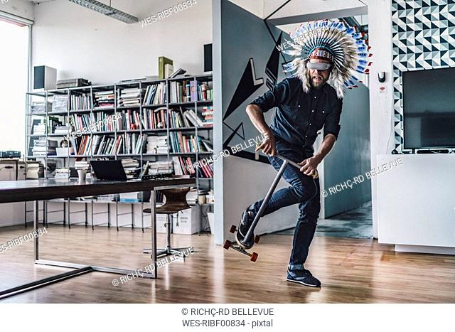Man wearing Indian headdress and VR glasses in office, using kick scooter